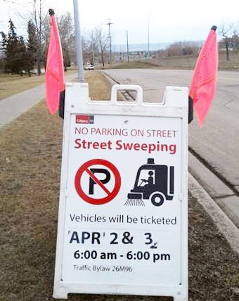 Street sweeping no parking sign