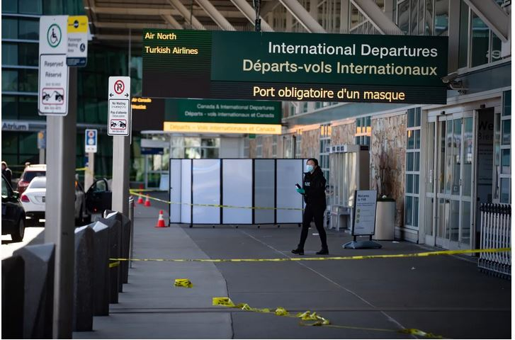 An RCMP officer works at the scene after a shooting at Vancouver International Airport on Sunday. (Darryl Dyck/The Canadian Press)